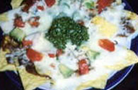 Hot tortilla chips topped with frijoles, salsa and cheese